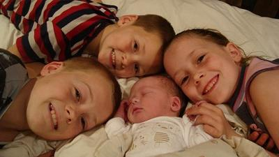 Siblings with their newborn baby brother