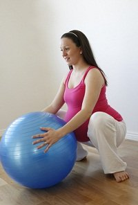 Woman squatting with a birth ball for support